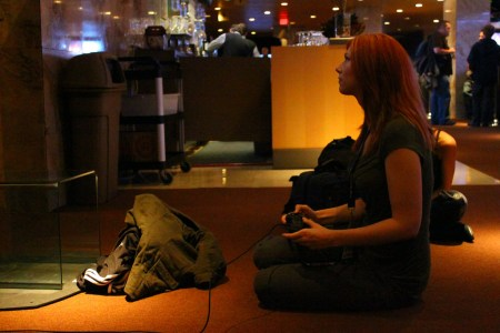Female gaming journalist sitting on floor, playing a video game. Photo by Shane K