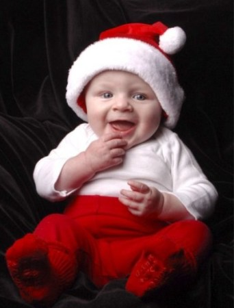 Smiling baby in Santa hat.