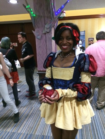Young black woman dressed in a snow white costume holding an apple in both hands.