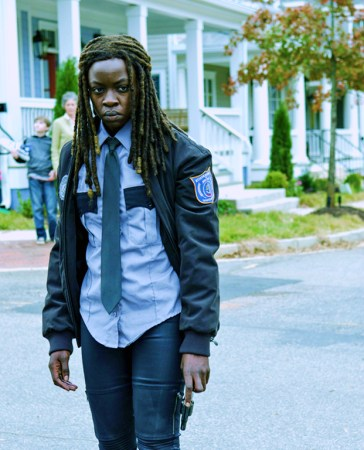 Michonne wearing her constable uniform looking stern holding a small ppistol in her left hand.