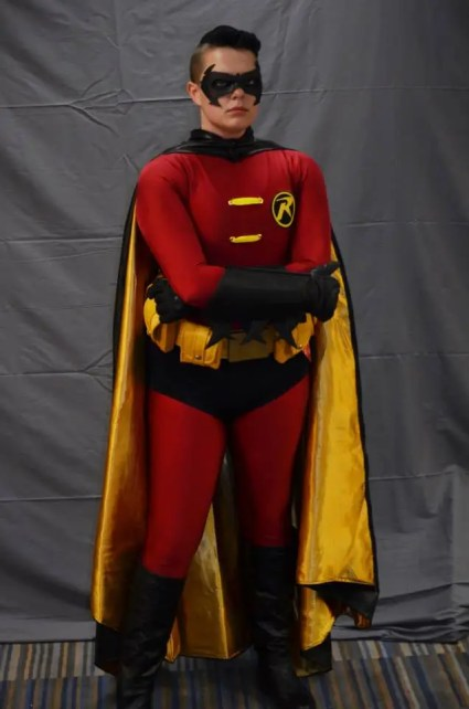 Tim stands stoic, dressed in a red, yellow, and black Robin costume.