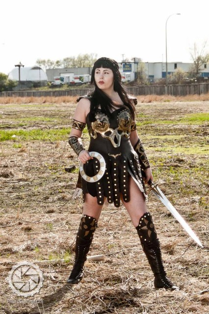 Ansley in a field, dressed as Xena: Warrior Princess.
