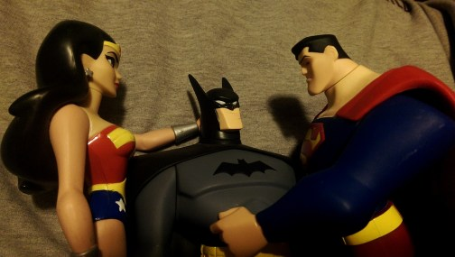 Wonder Woman, Batman, and Superman action figures in an intimate embrace