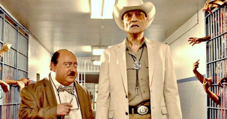 A short mustached man in a bow tie talks to a tall man in a cowboy hat who looks shocked in Human Centipede 3