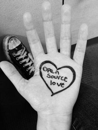 "Black and white photo of a light skinned hand with a heart drawn on the palm, and in the center of the heart are the words ""Open source love""."