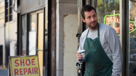 Man in green smock stands outside storefront holding a cup of coffee in The Cobbler