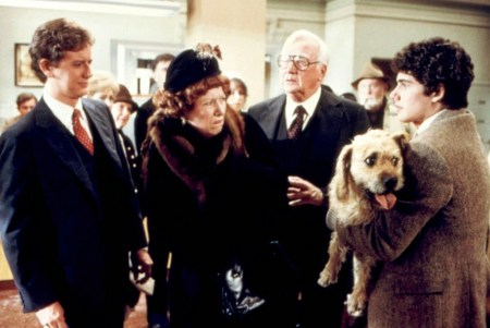 Left to right - a man in a suit, elderly woman in fancy dress coat and hat, elderly man in a suit, and the boy in a suit holding his dog. The woman is glaring at the teenage boy.