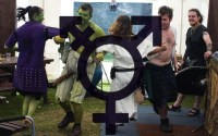 LARPers dancing in a tent, with the Transgender logo transposed over the photo