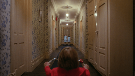The son on his tricycle facing down a hall. The creepy twin ghosts are at the end of the hallway being creepy.