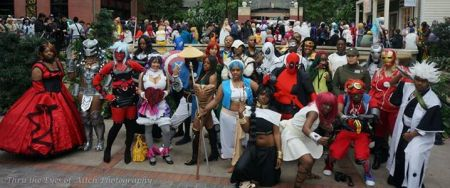A photo of black cosplayers of various costumes at a convention.