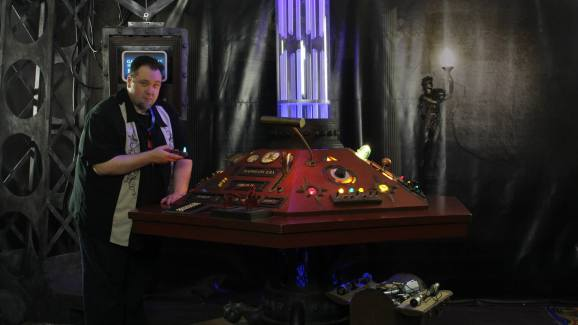 Photo of Christopher Jones next to a Doctor Who TARDIS console
