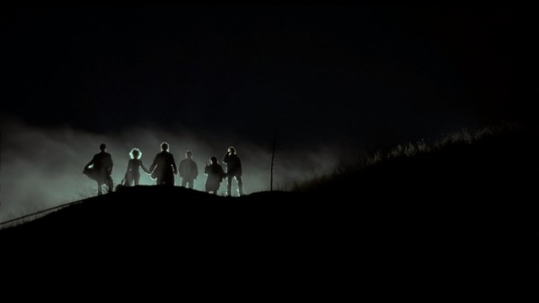 Silhouette of six people standing in the distance, coming out of a dusty background with backlighting.