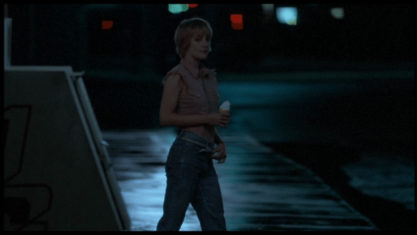 Screenshot of Jennie Wright as Mae standing on the road and holding an ice cream cone.