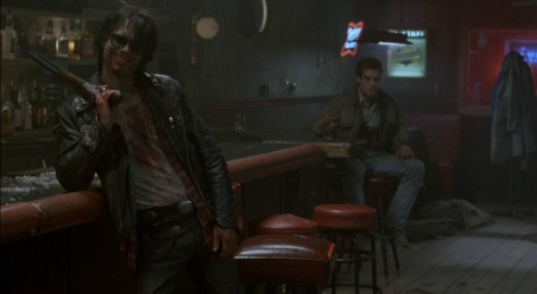 Screenshot of two men in a bar, one of them bloodied, smiling, and gun-toting.