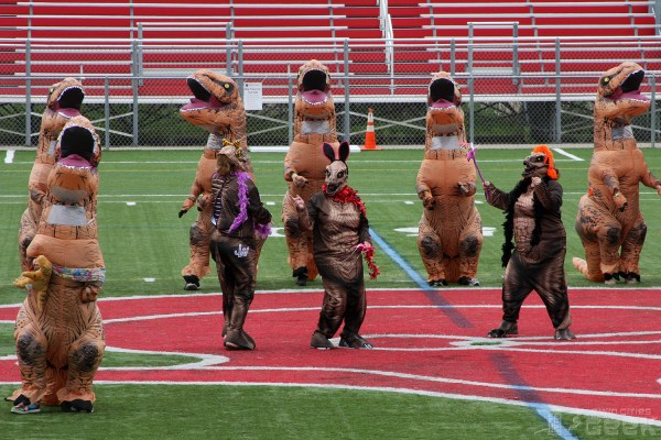 A group of humans in T-Rex costumes dances on a football field. Three T-Rexes with colored feather boas dance in the center of the photo.