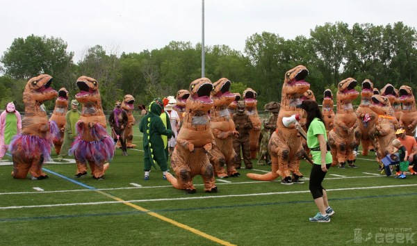 A group of humans in T-Rex costumes stand gathered on a football field. A woman with a megaphone stands in front of them, speaking into the megaphone.