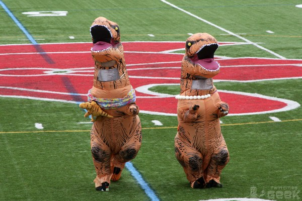 Two humans in inflatable T-Rex costumes jog side-by-side on a football field.