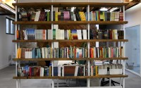 Freestanding woodne shelves filled with books in the middle of an office space