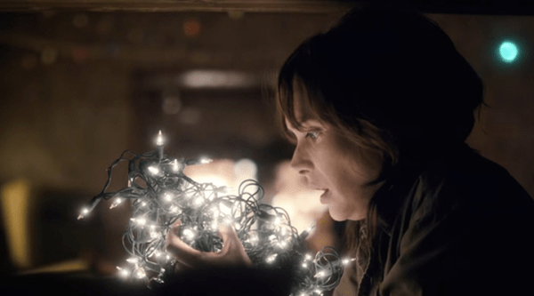 Joyce (Winona Ryder) looks at a handful of glowing Christmas lights