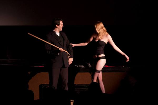 A man with a yardstick and a woman in burlesque clothing
