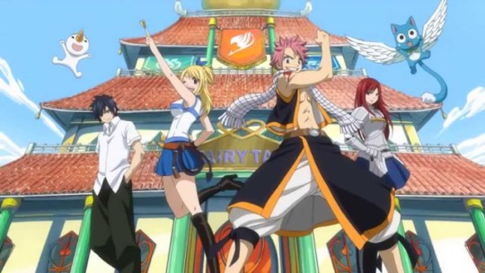 The five main characters of Fairy Tail striking triumphant poses in front of the guild building