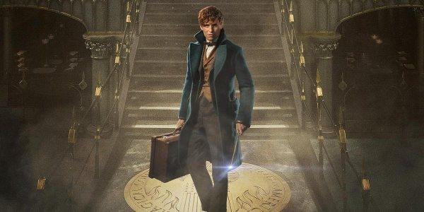Eddie Redmayne as Newt Scamander holding a suitcase and a wand