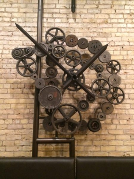 Abstract sculpture composed of gears and wheels mounted on a brick wall. Two spikes criss-cross in front of the gears to give the piece an overall clock appearance.