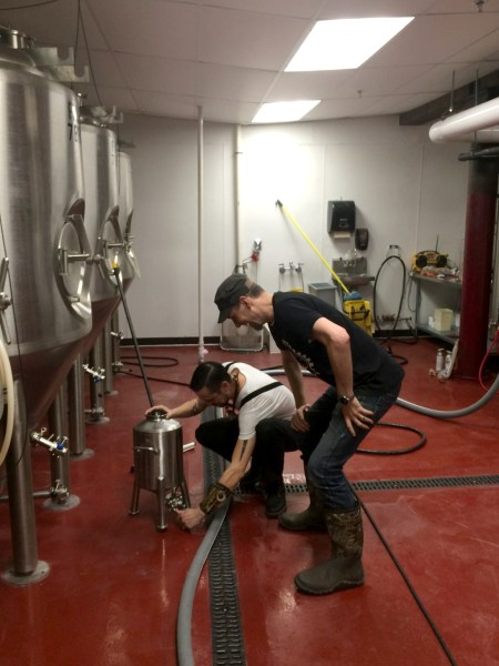 Two men working with brewing equipment