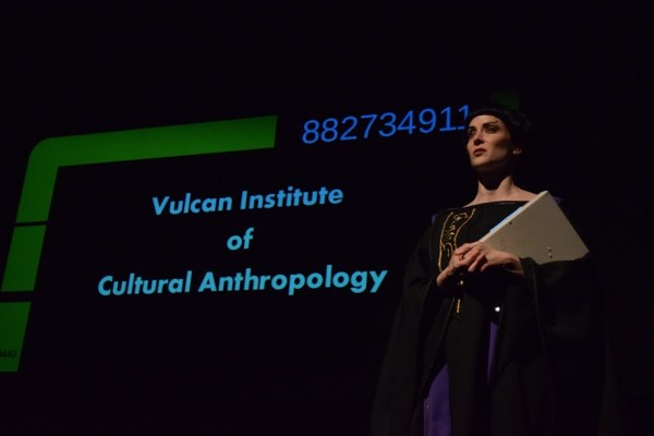 "Vulcan in front of screen that reads, ""Vulcan Intitute of Cultural Anthropology"""