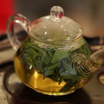 A small glass teapot filled with brewing tea leaves