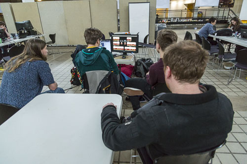 A group of four designers watch their game on a single monitor. (Photo T.A. Wardrope)