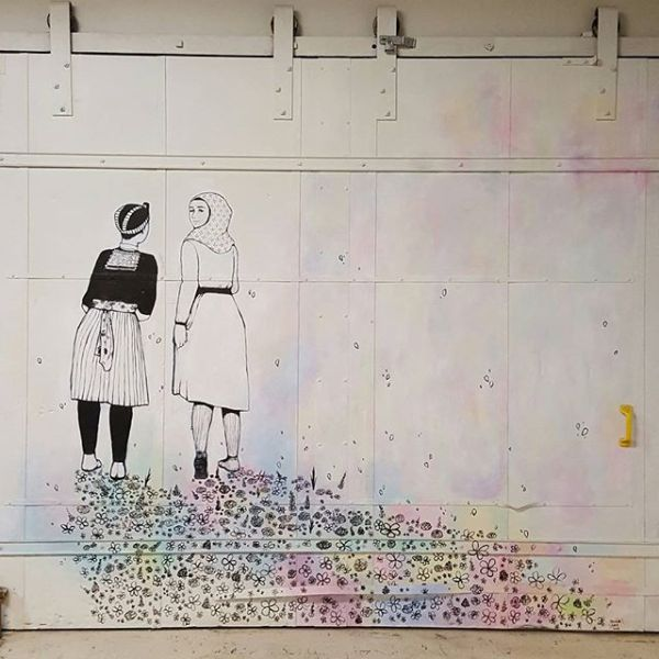 Mural on a large sliding door. Background is white. Two girls walk away from the viewer, leaving a trail of flowers in their path. One girl, wearing a headscarf, is looking back over her shoulder at the viewer.