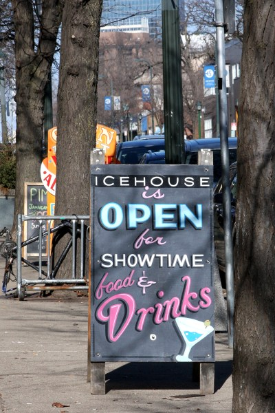 "A sandwich board reading ""Icehouse is open for showtime, food & drinks"""