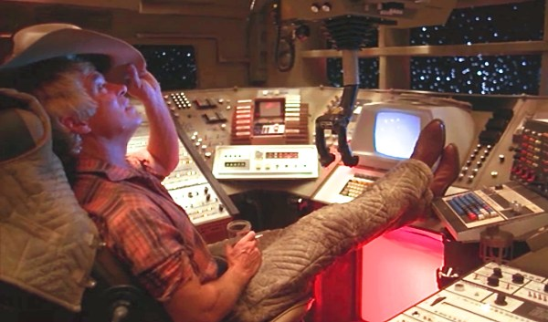 Space Cowboy sitting at a control panel.