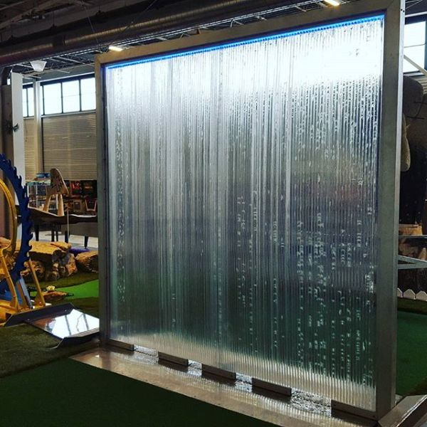 An 8 foot by 8 foot window stands in the middle of the mini golf green. Water runs down the window, creating the illusion of a waterfall. As golf balls pass below the window, changes in the water fall patterns are triggered.
