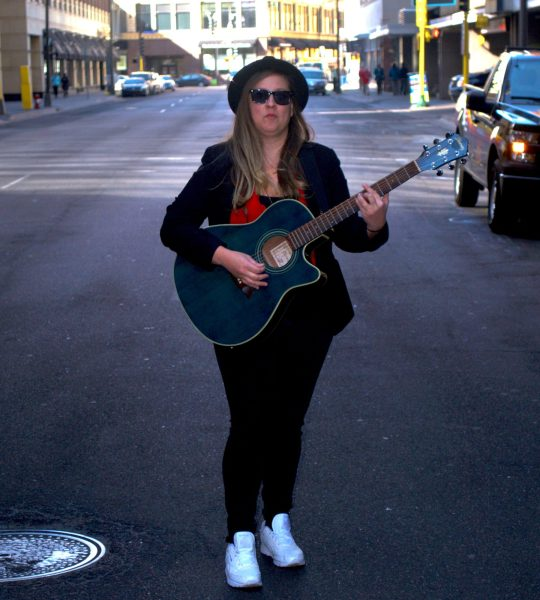 A woman stands in the middle of an empty street, holding a guitar. She is wearing a fedora and sunglasses, unsmiling.