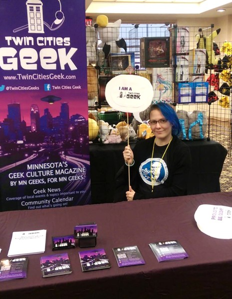A woman with blue hair at a table with Twin Cities Geek branding