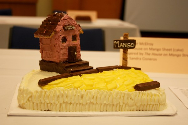 A cake featuring a house with a sign reading MANGO
