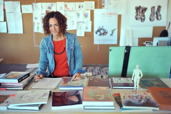 Illustrator Wendy MacNoughton standing in front of a table covered in sketchbooks and textbooks on illustration. Wendy is holding a pencil over an open sketchbook and smiling at the camera.