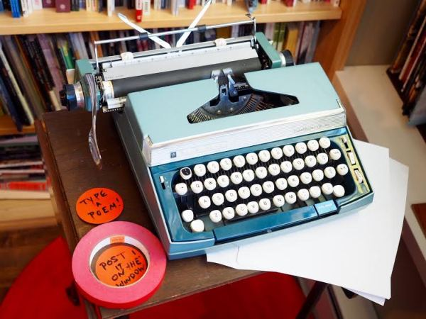 "A typewriter inviting visitors to ""Type a poem!"""