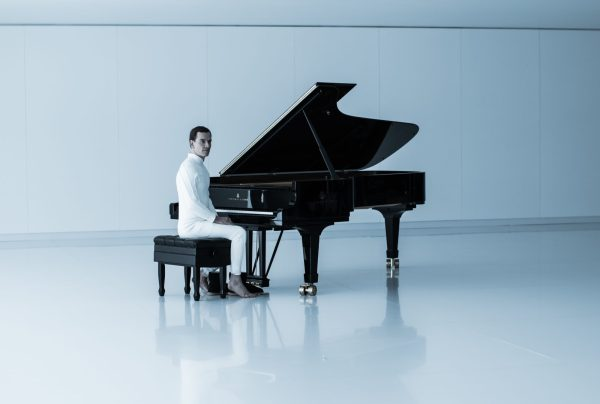 Michael Fassbender's character David dressed in spotless white, in a white room, sitting at a black grand piano.