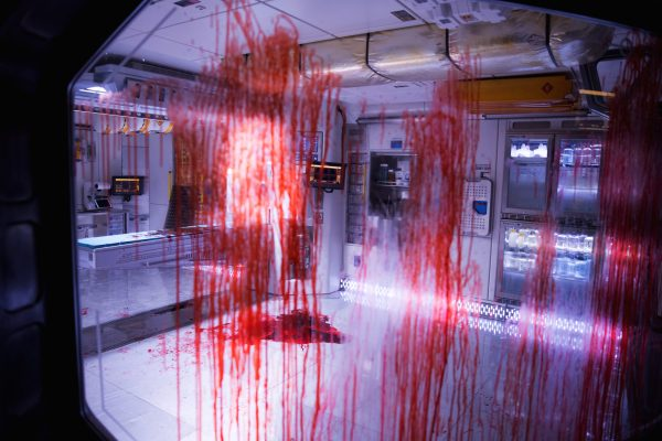 A lab with a large pool of blood on the floor and streaking down the windows.