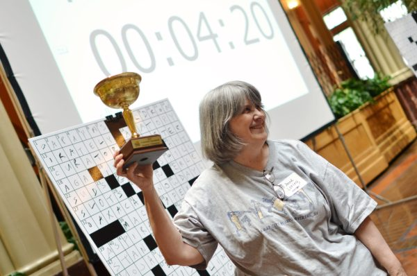 A 2016 crossword winner holds up her trophy