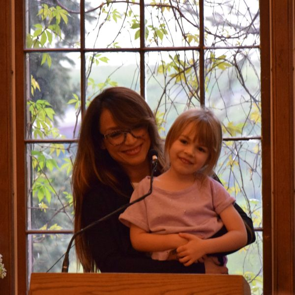 Mayte Garcia holding up her five-year old daughter, Gia, before reading in the University Club. Photo by Paul Patane