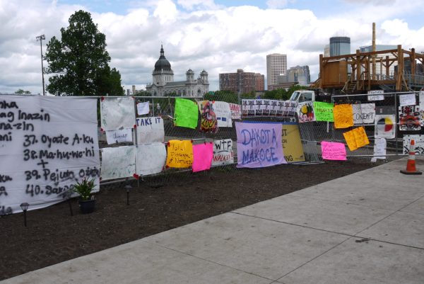 A view of the protest site on Memorial Day, with the fences completely covered by signs critical of Walker and <i>Scaffold</i>