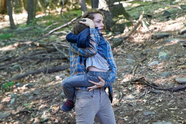 A woman cradles a young child in her arms while walking through the woods during the day.