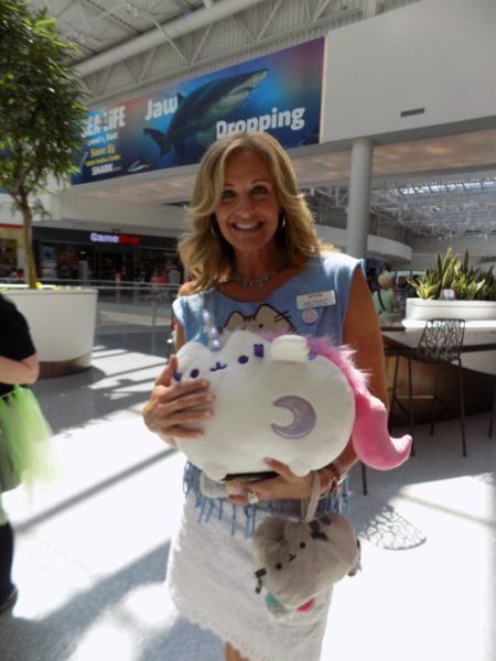 A woman holds the unicorn Pusheen plush