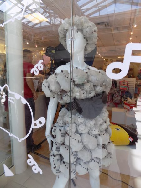 A mannequin in a window in a dress and hat made from small brown Pusheen plushies
