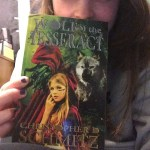 "[girl holding a book cover closely to her face. Book cover says ""Wolf of the Tesseract]"