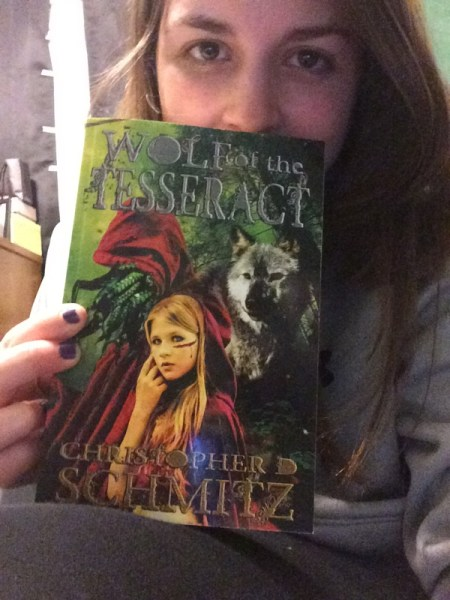 Article author holding a copy of Wolf of the Tesseract.